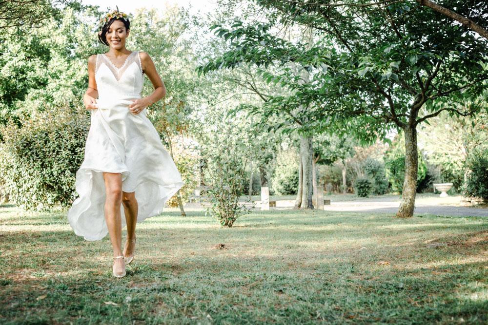 Mariée qui court dans l'herbe